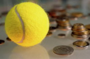 Finances Posters - Tennis ball next to numerous piles of coins Poster by Sami Sarkis