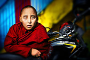 Red Robe Posters - The boy monk in red robe standing beside a motorcycle in a Buddh Poster by Max Drukpa