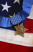 Courage Photo Metal Prints - The Medal Of Honor Rests On A Flag Metal Print by Stocktrek Images