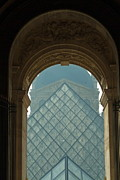 Art Museum Prints - The pyramid of the Musee du Louvre seen through an arched window Print by Sami Sarkis