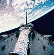Space Shuttle Posters - The Space Shuttle With Its Open Cargo Bay Orbiting Above The Earth Poster by Stockbyte
