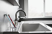 Sink Prints - Toothbrushes in a Glass on a Sink Print by Jetta Productions, Inc