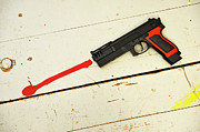 Social Issues Prints - Toy gun on floor with red paint Print by Sami Sarkis