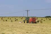Bailing Hay Photos - Tractor bailing hay in a field at harvest time by Andy Smy