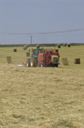 Summer Photo Framed Prints - Tractor bailing hay in a field at harvest time Pt Framed Print by Andy Smy