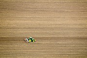 Middle Ground Photos - Tractor Ploughing A Field by Photostock-israel