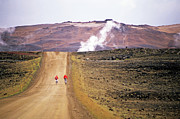 Power Plants Prints - Two bikers on a dirt road leading to a geothermal power station at Myvatn Print by Sami Sarkis