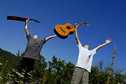 Serene People Posters - Two boys standing in meadow holding guitars in outstretched arms Poster by Sami Sarkis
