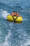 Laughing Posters - Two children on inflatable ring Poster by Sami Sarkis