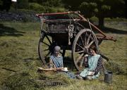 Hayfield Prints - Two Girls Eat Lunch In A Hayfield Print by Clifton R. Adams