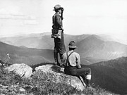 Sitting On Rock Prints - Two Men At Mountain Summit, One Using Binoculars (b&w) Print by Hulton Archive