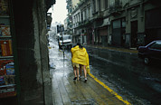 National Peoples Framed Prints - Two People Share A Raincoat Framed Print by Pablo Corral Vega