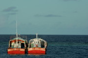 Docked Boats Prints - Two red fishing boats moored side by side in the blue ocean Print by Sami Sarkis