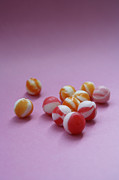 Sweet Success Prints - Unwrapped Hard Candies On Pink Paper Print by Asia Images