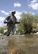 Trudging Posters - U.s. Army Soldier Crosses A Stream Poster by Stocktrek Images