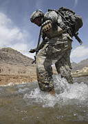 Trudging Posters - U.s. Army Specialist Crosses A River Poster by Stocktrek Images