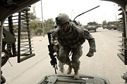 Baghdad Posters - U.s. Army Specialist Entering A Stryker Poster by Stocktrek Images