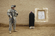 Villagers Posters - U.s. Army Specialist Guards An Iraqi Poster by Stocktrek Images
