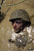 Trudging Posters - U.s. Marine Advancing Through An Poster by Stocktrek Images