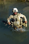 Trudging Posters - U.s. Marine Crosses A Stream Poster by Stocktrek Images