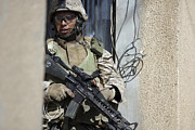 Assault Rifles Photo Framed Prints - U.s. Marine Takes Cover Behind A Wall Framed Print by Stocktrek Images