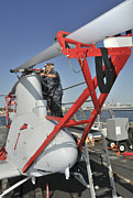 Rotor Blades Photo Prints - U.s. Navy Mechanic Removes A Rotor Print by Stocktrek Images