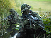 Kneeling Photo Prints - U.s. Navy Seals Cross Through A Stream Print by Tom Weber