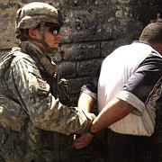 Combat Gear Prints - Us Soldier Cuffs An Iraqi Man Suspected Print by Everett
