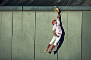 Sports Clothing Posters - Usa, California, San Bernardino, Baseball Player Making Leaping Catch At Wall Poster by Donald Miralle