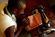 African Cloth Framed Prints - Using A Sewing Machine, Uganda Framed Print by Mauro Fermariello