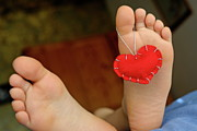 Surprise Prints - Valentine heart hanging on girls barefeet Print by Sami Sarkis