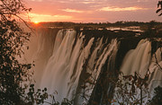 Victoria Falls Photos - Victoria Falls With Sun On Horizon, Victoria Falls, Zimbabwe by Denny Allen