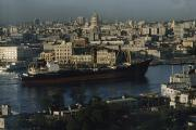 Ocean Scenes Prints - View Of City And A Massive Freighter Print by James L. Stanfield