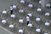 Piazza San Marco Prints - Waiters at empty cafe terrace on Piazza San Marco Print by Sami Sarkis