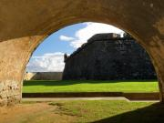 National Historic District Framed Prints - Walls of San Felipe Del Morro Viewed Through  an Arch Framed Print by George Oze