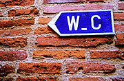Directional Signage. Prints - Water closet sign on a brick red wall Print by Sami Sarkis