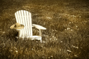 Adirondack Chair Posters - White chair with straw hat in a field Poster by Sandra Cunningham