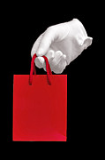 Glove Framed Prints - White glove holding a red gift bag Framed Print by Richard Thomas