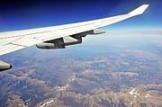 Sami Sarkis - Wing of flying airplane over Wyoming mountains