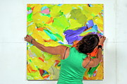 Art Product Photo Prints - Woman adjusting a painting Print by Sami Sarkis