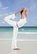 Posture Prints - Woman doing yoga on the beach Print by Setsiri Silapasuwanchai