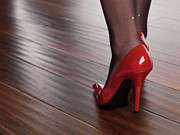 Business Woman Prints - Woman in Red High Heels Walking on Hardwood Floor Print by Oleksiy Maksymenko