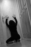 Despair Prints - Woman kneeling in corridor with hands on closed door Print by Sami Sarkis