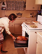 35-39 Years Posters - Woman Removes Cooked Turkey From Oven Poster by Archive Holdings Inc.