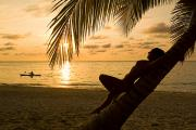 Seacoast Prints - Woman Resting On A Palm Tree At Sunset Print by Richard Nowitz