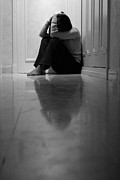 Anxiety Photo Framed Prints - Woman sitting in corridor with head in hands Framed Print by Sami Sarkis