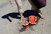 Misfortune Prints - Woman standing by broken watermelon on asphalt Print by Sami Sarkis