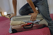 Excess Prints - Woman trying to close overflowed suitcase on bed Print by Sami Sarkis