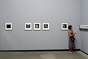 Woman Watching Photos At Exhibition Print by Sami Sarkis