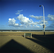 Shadows Photos - Wooden bench in front of ocean.Deauville. France by Bernard Jaubert
